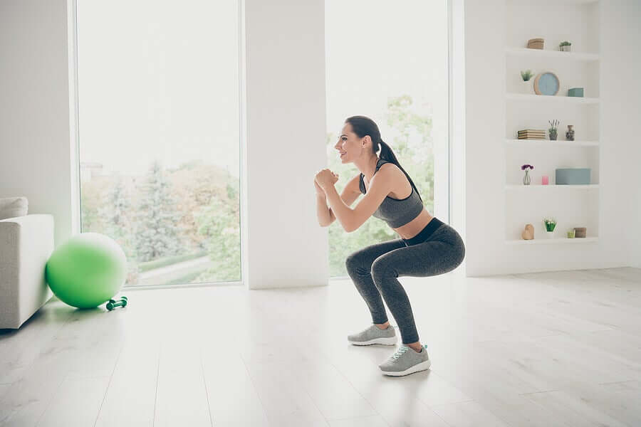 A woman performing squats as knee-strengthening exercises.