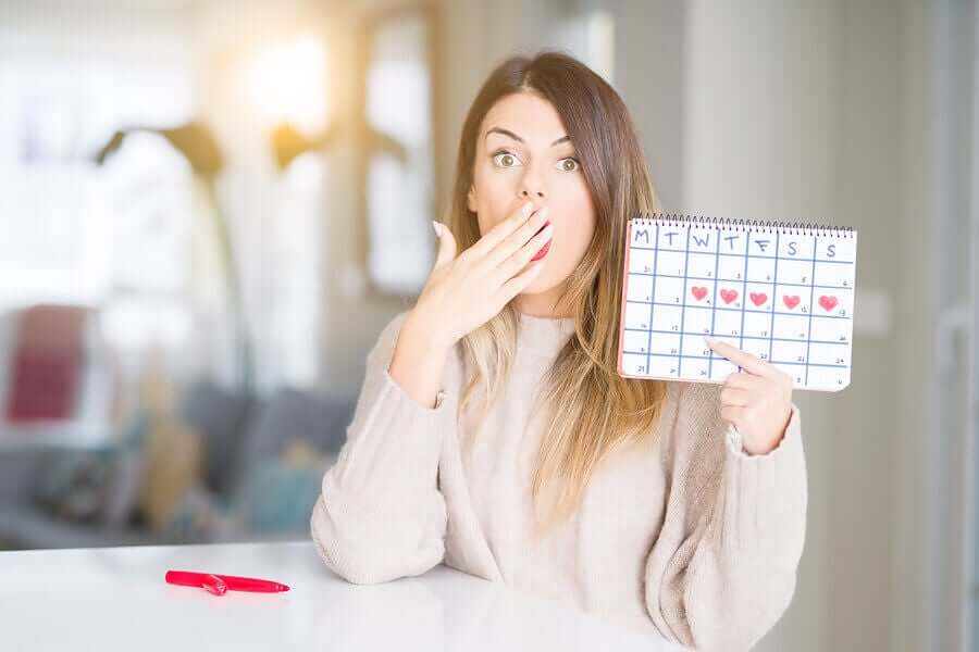 A woman holding up a calendar of her menstrual cycle.