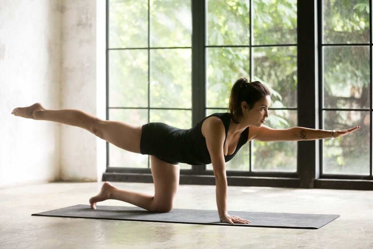 A woman stretching on a mat.