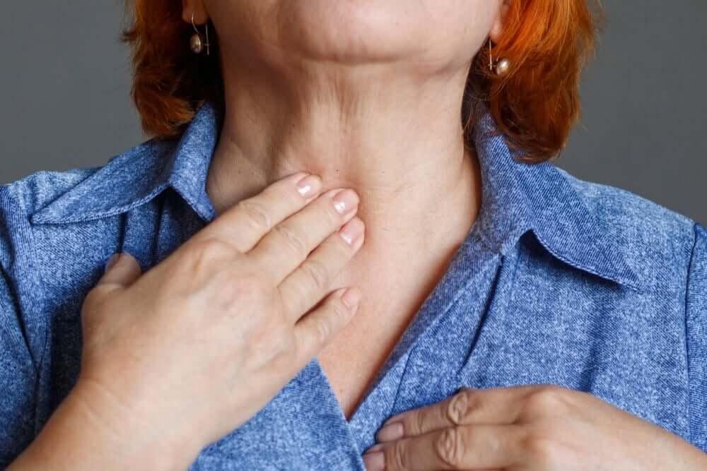 An elderly woman toughing her throat.