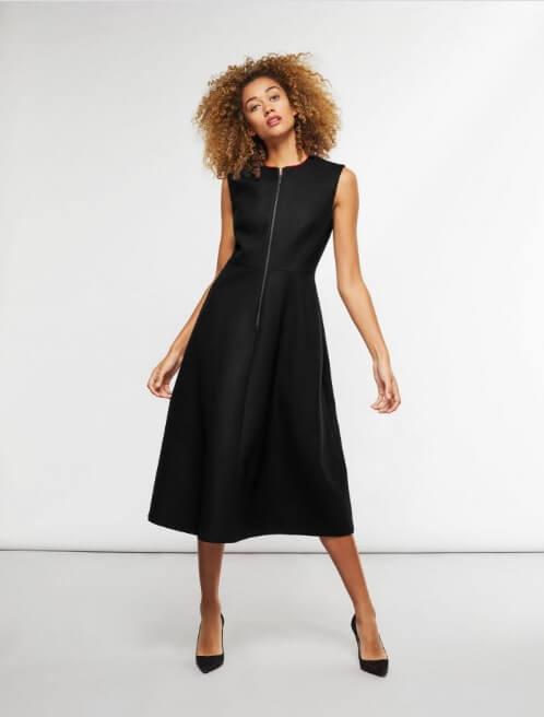 A woman wearing a black medium-length dress.