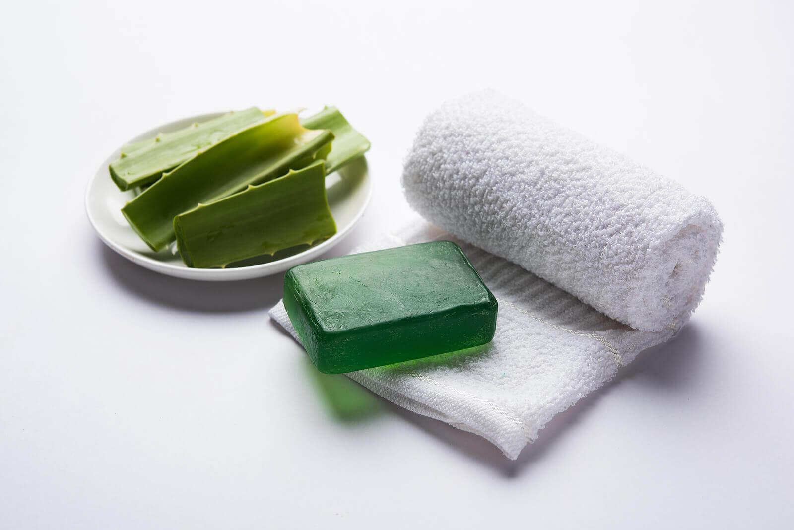 Aloe pieces, aloe soap, and a white towel.