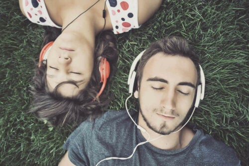 two people lying on the grass with headphones on