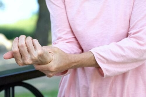 woman with pain in her wrist holding her wrist