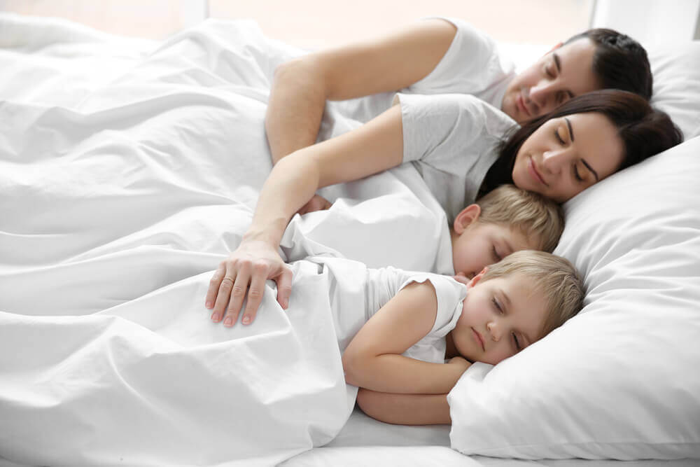 A family sleeping in bed