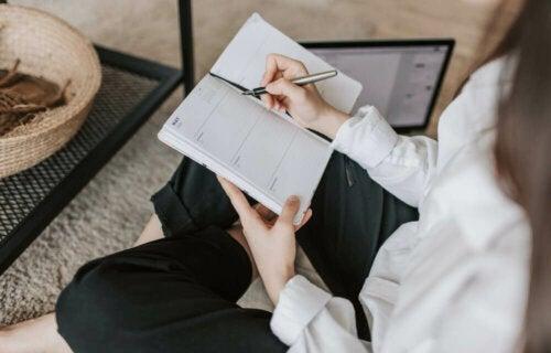 A woman writing down her SMART goals.
