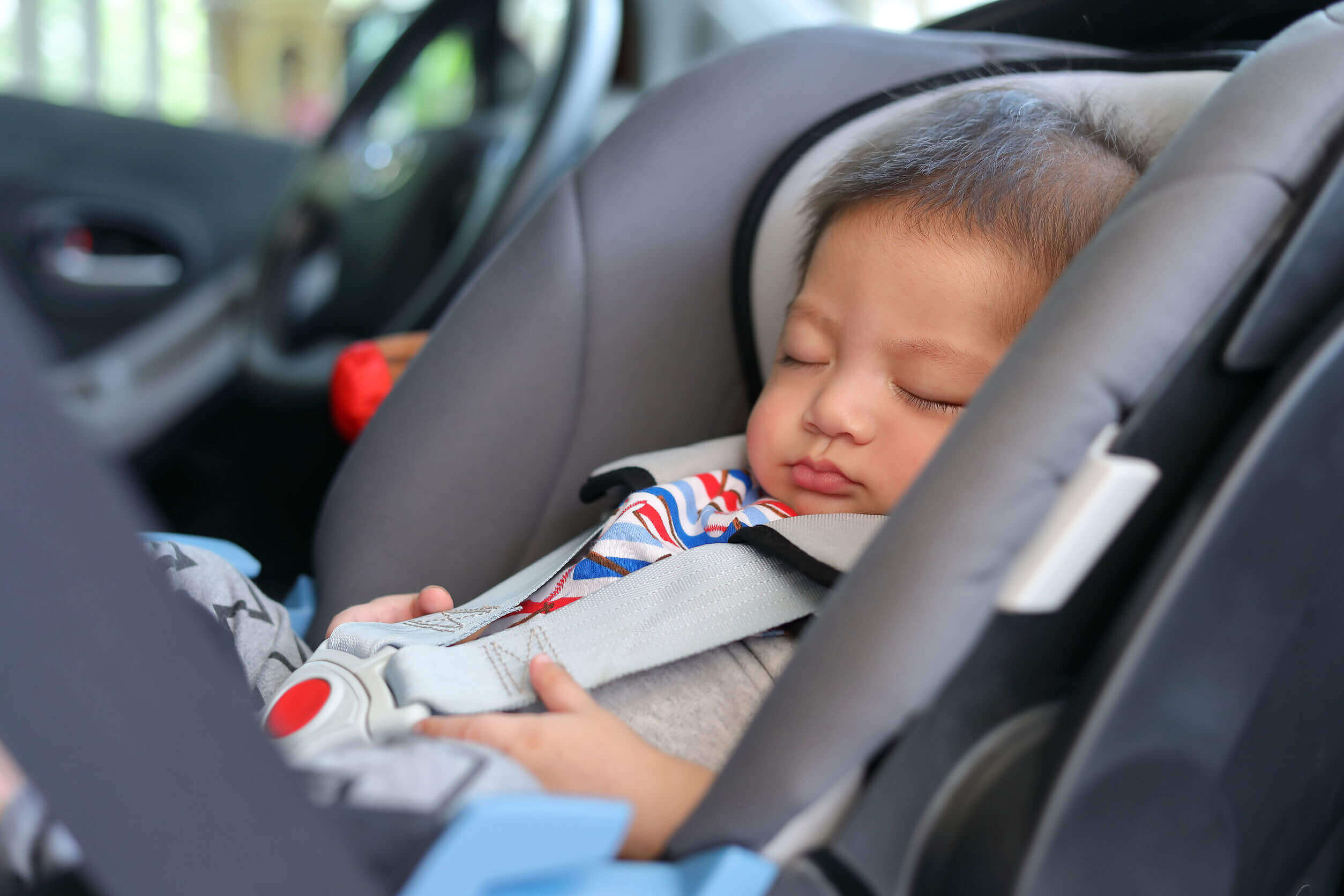 An infant sleeping in a car seat.