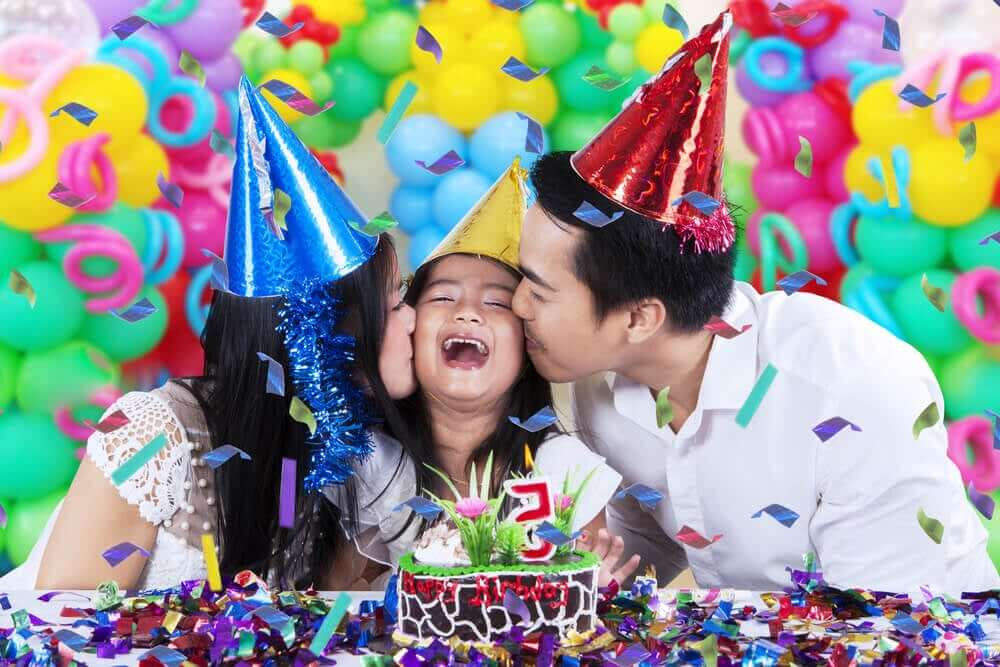 Parents kissing their daughter on the cheek during her birthday party.