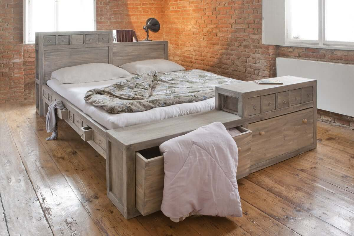 A wooden bed with lots of drawers, both large and small.