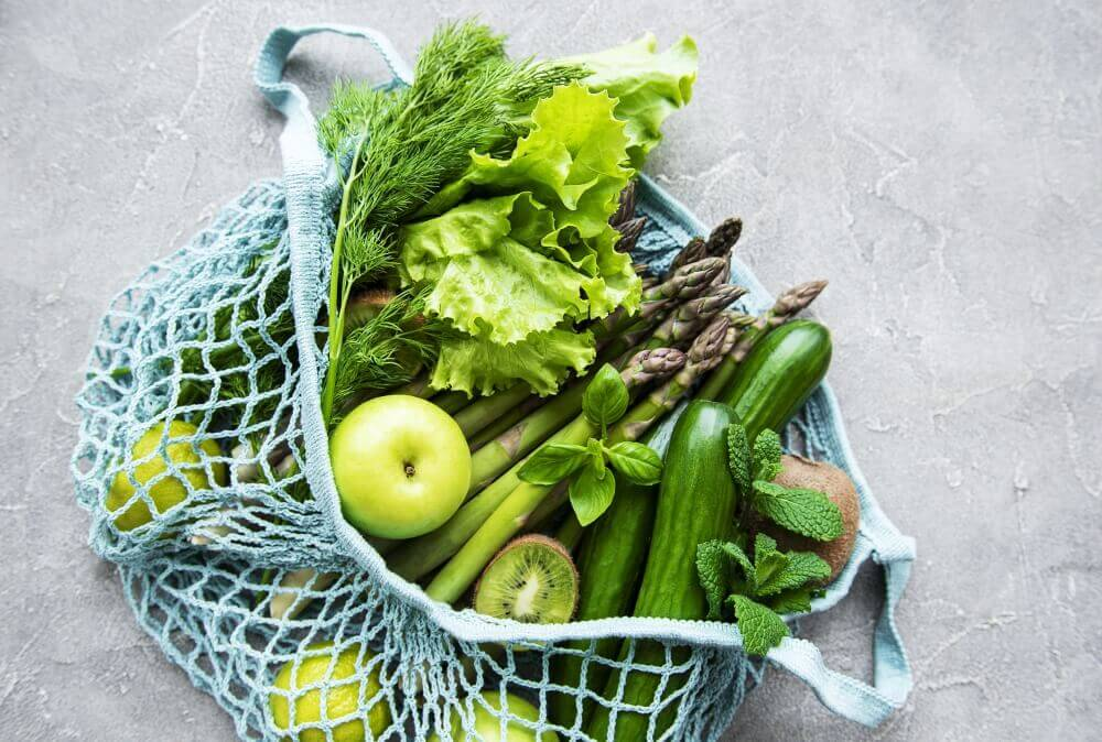 A bag of green fruits and vegetables.