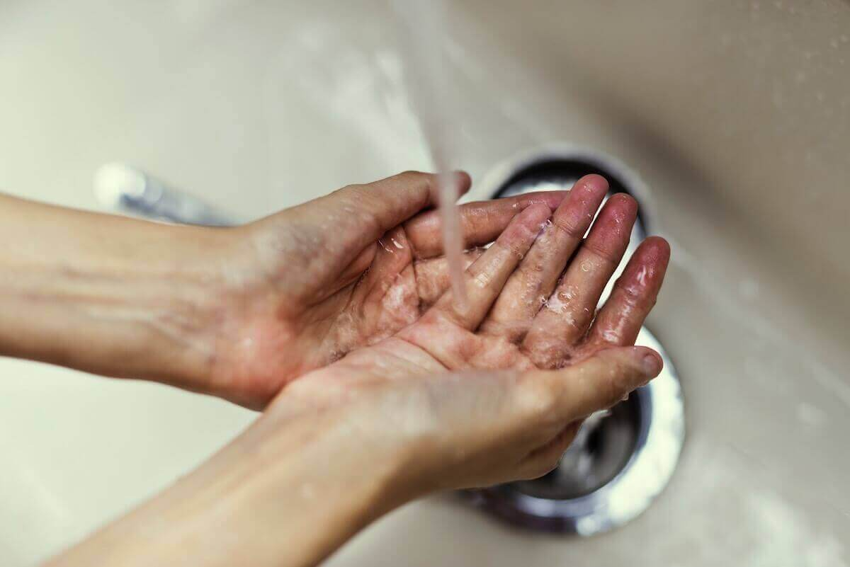 A woman rinsing her hands under the faucet.