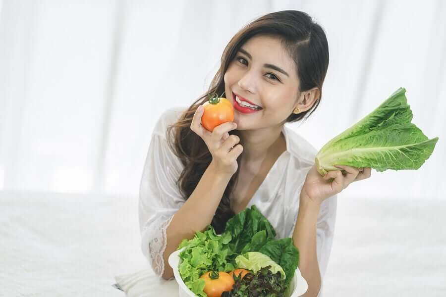 A woman eating fresh vegetables.