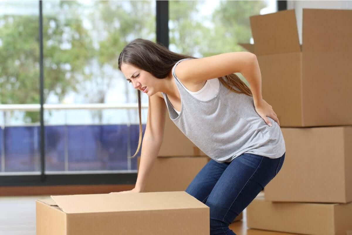A woman with lower back pain from lifting a heavy box.
