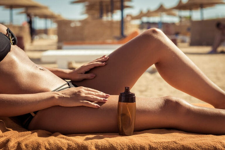 A woman laying out at the beach with a bottle of tanning oil next to her.