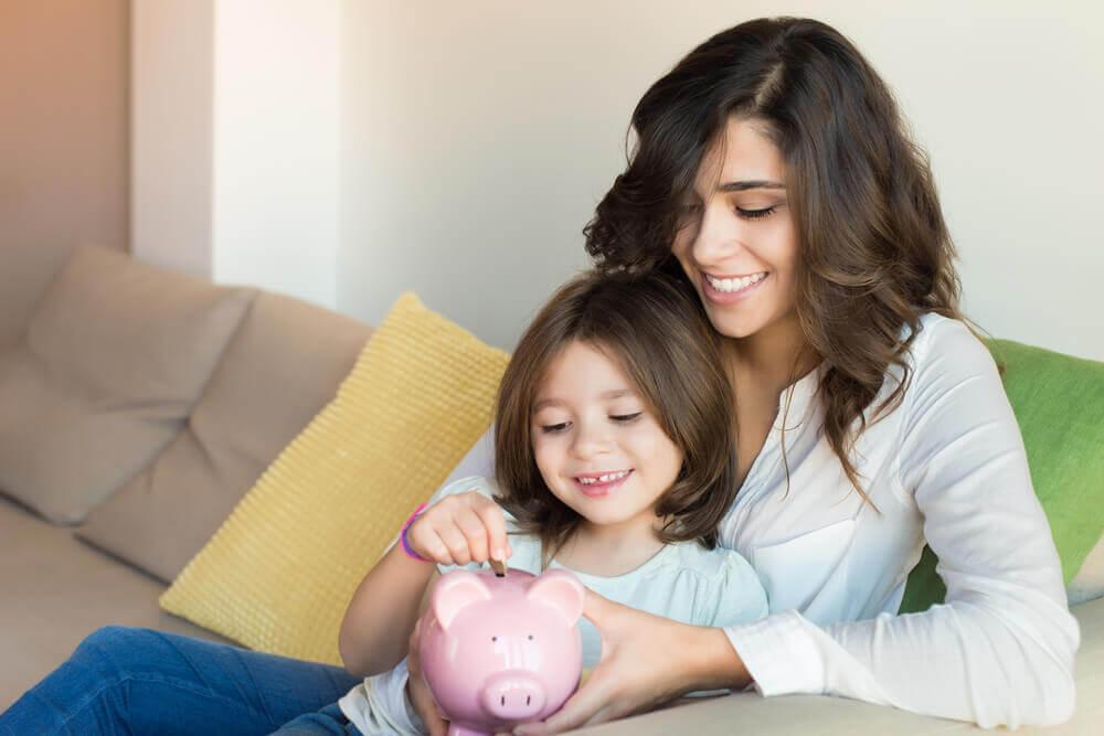 Młoda dziewczyna wkłada pieniądze do świnki skarbonki siedząc na kolanach mamy.