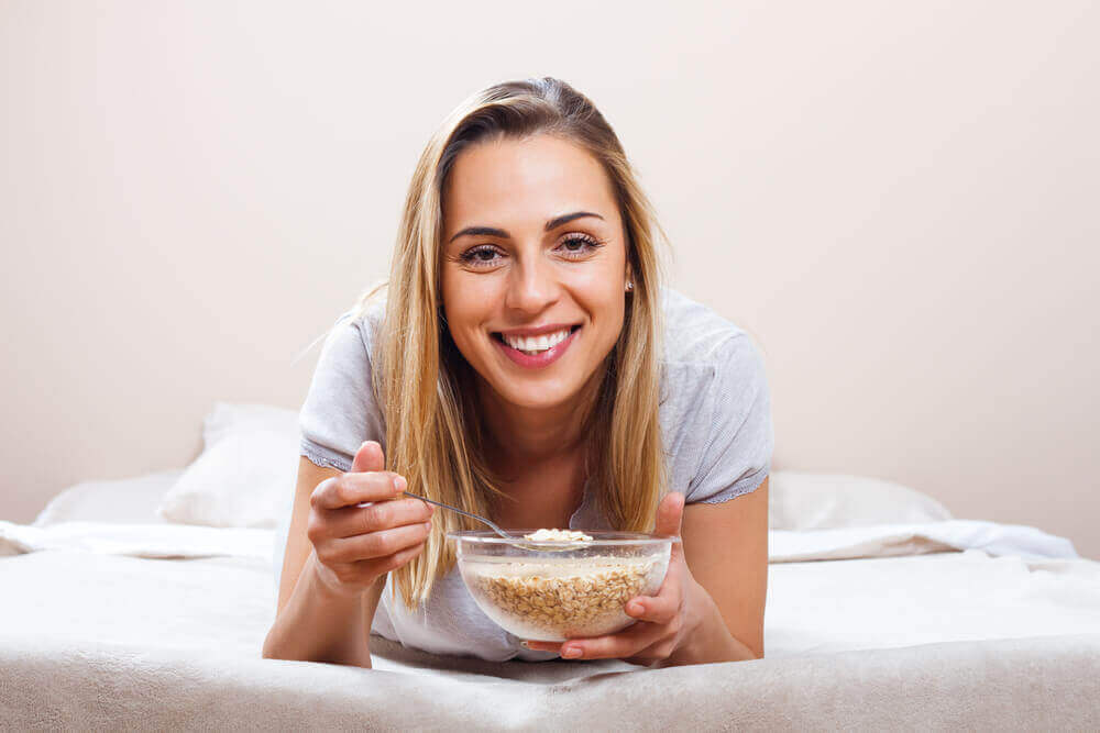 A woman eating a bowl of cereal.