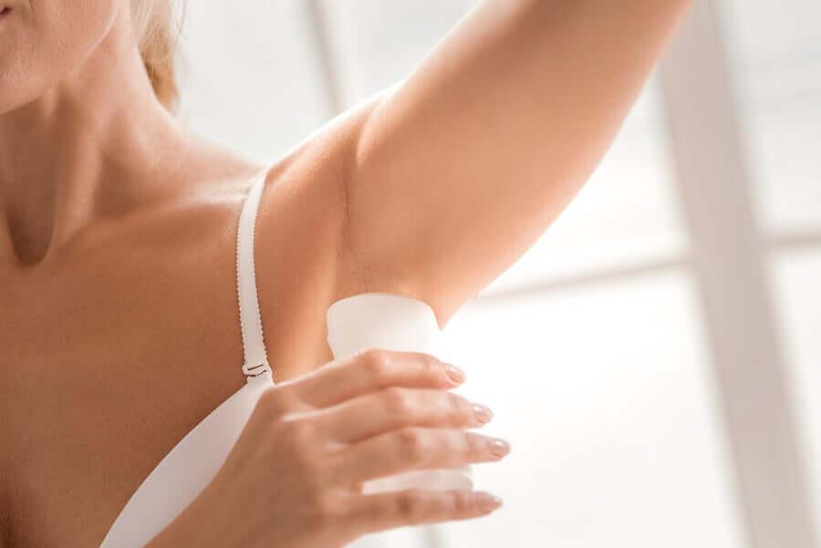 A woman applying deodorant.