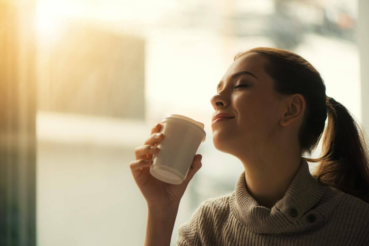 A woman sitting in a cafe drinking coffee.