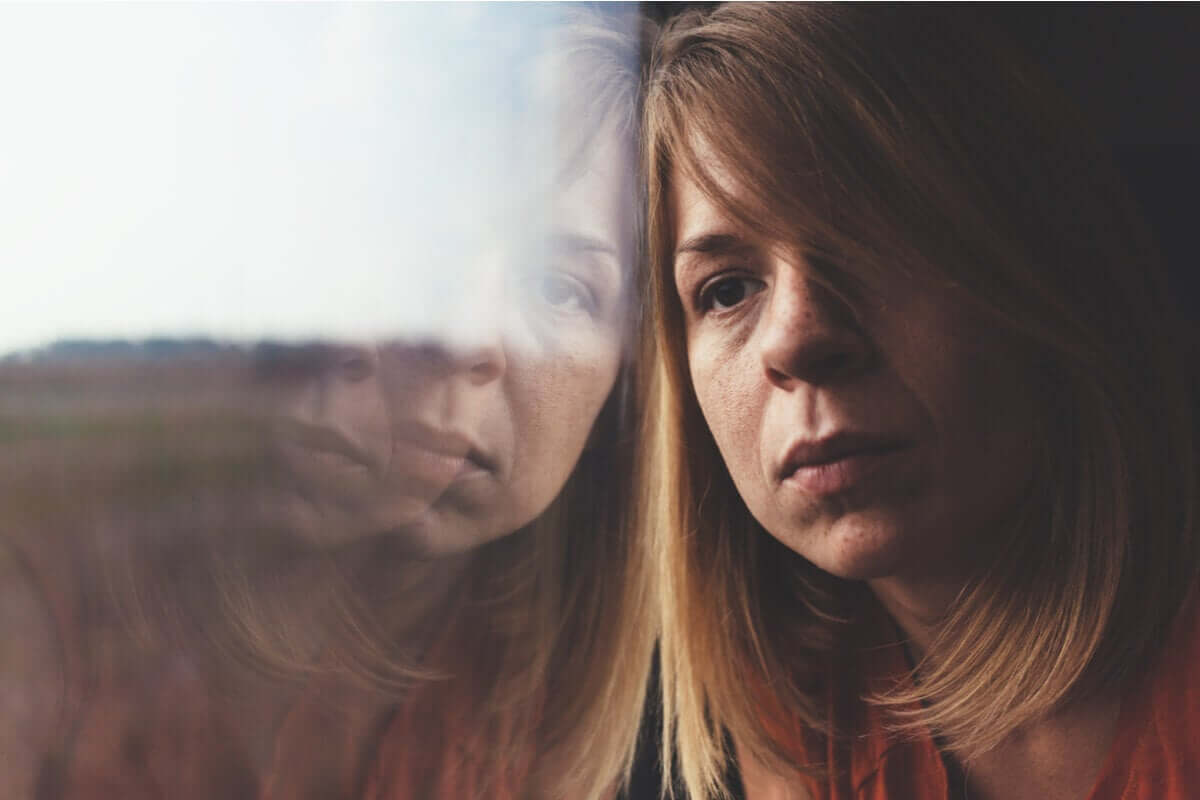 A woman leaning up against a window feeling discouraged.
