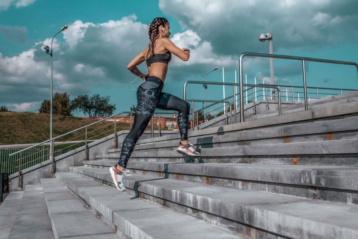 A woman running up bleachers.