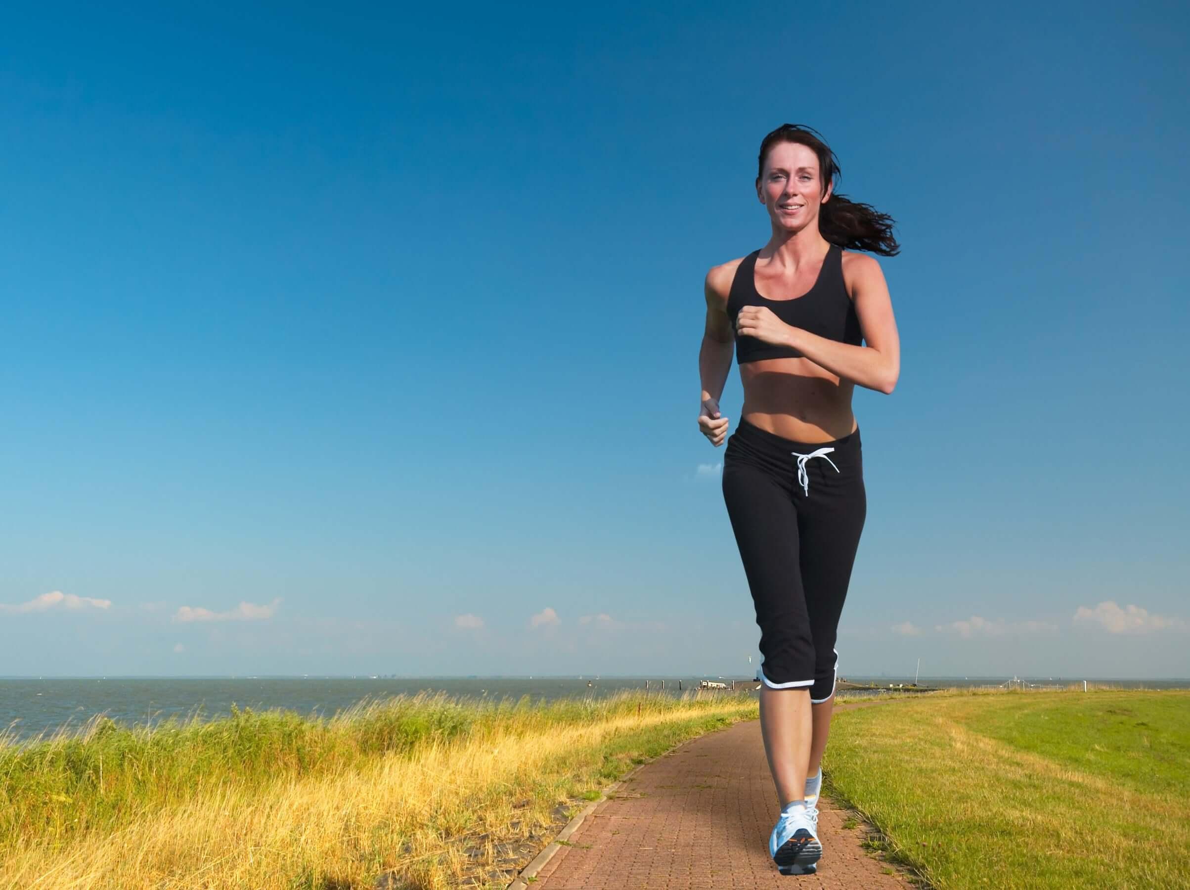 A woman running near the ocean.