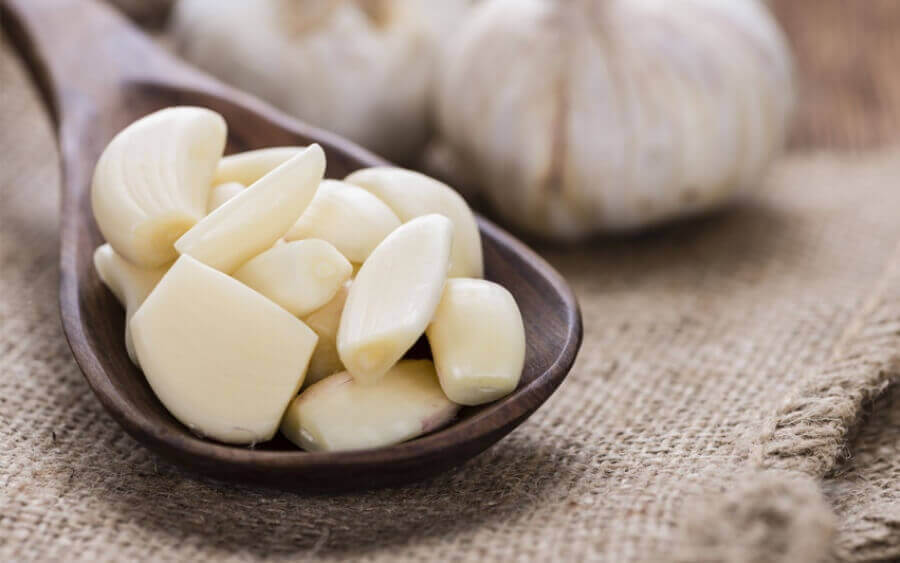 Peeled garlic cloves in a wooden spoon.