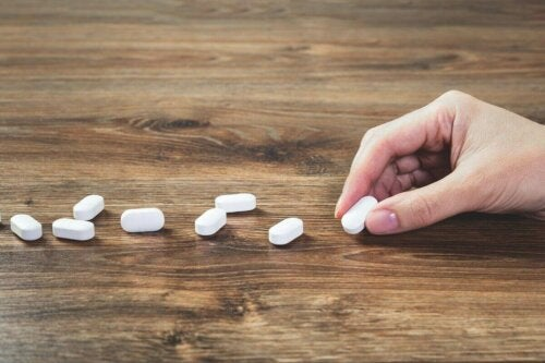 hand laying out pills on a wooden table