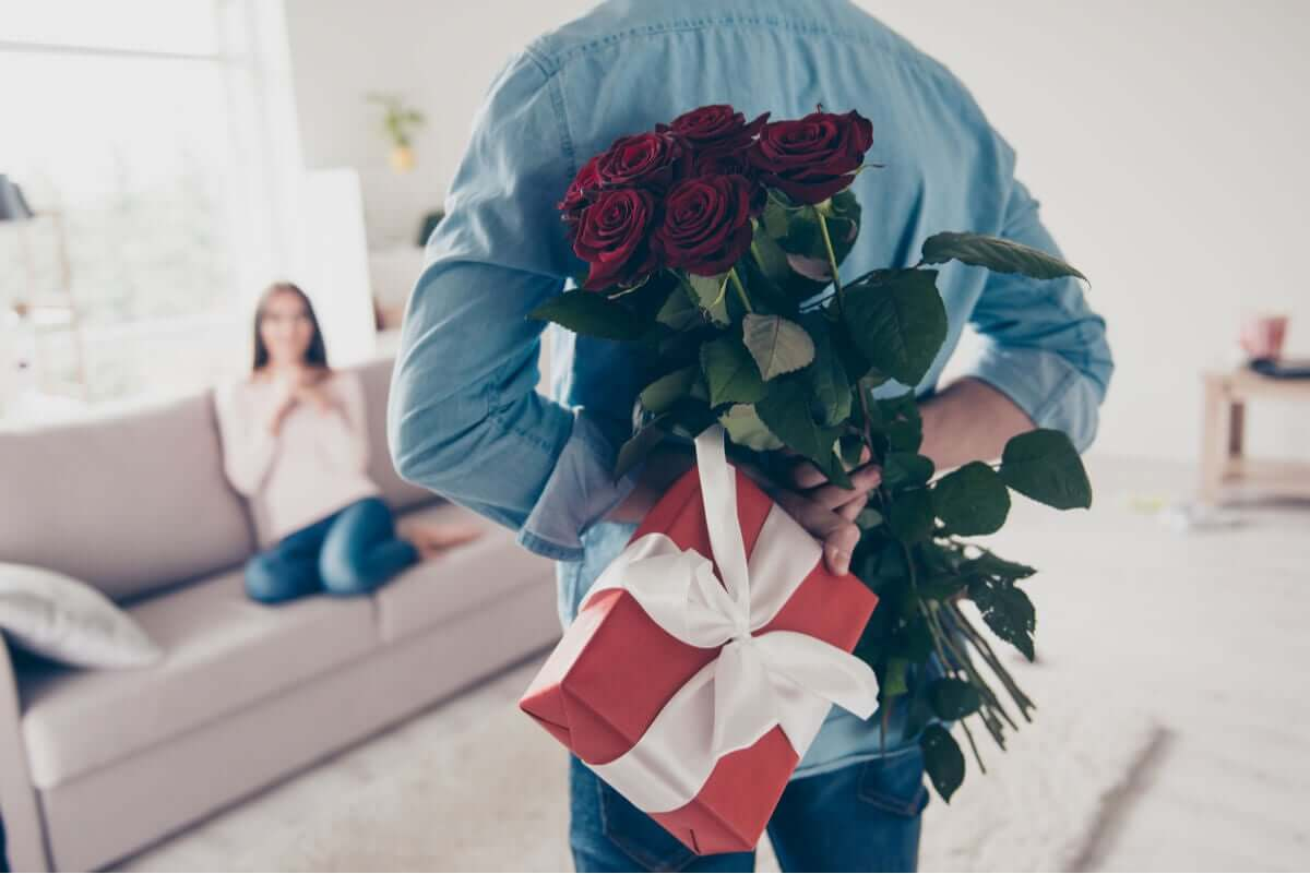 A man surprising his partner with flowers and a gift.