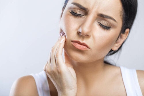 woman with touching her cheek in pain to indicate painful tooth