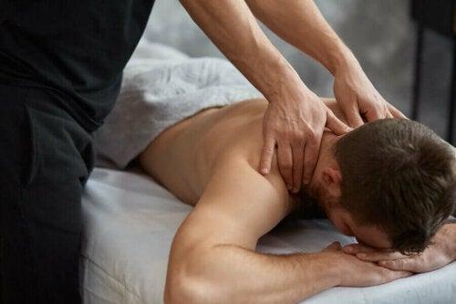 A person massaging a man.