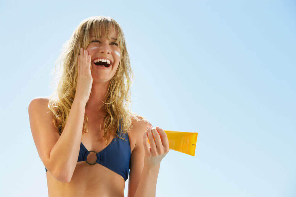 A woman putting on sunscreen