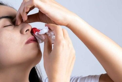En kvinde, der forsøger at stoppe næseblod