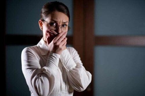 En kvinde, der oplever araknofobi, holder sig for munden