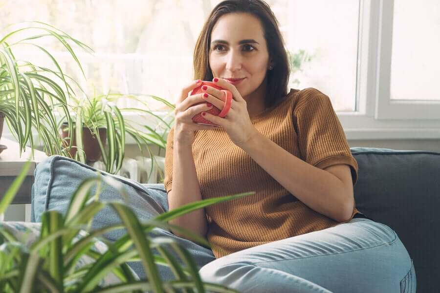A woman sitting on the couch, drinking a cup of coffee.