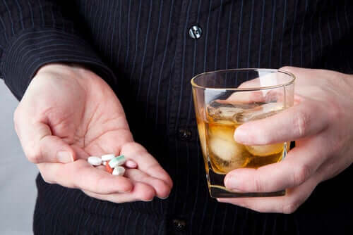A person mixing pills with alcohol.