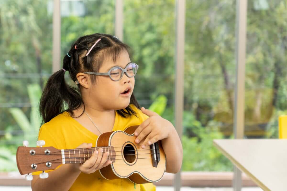 A child with Down syndrome playing the guitar.