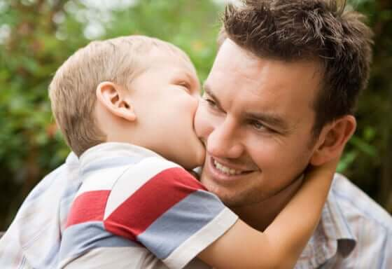 A small boy kissing his dad on the cheek.