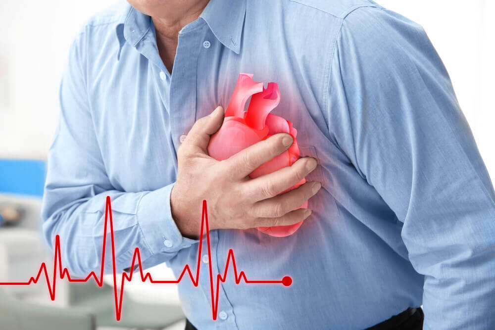 A man suffering from a heart attack, clutching his chest.