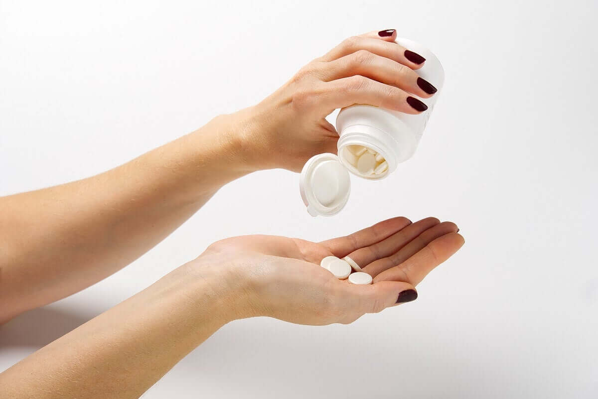 A woman pouring out pills into her hand.