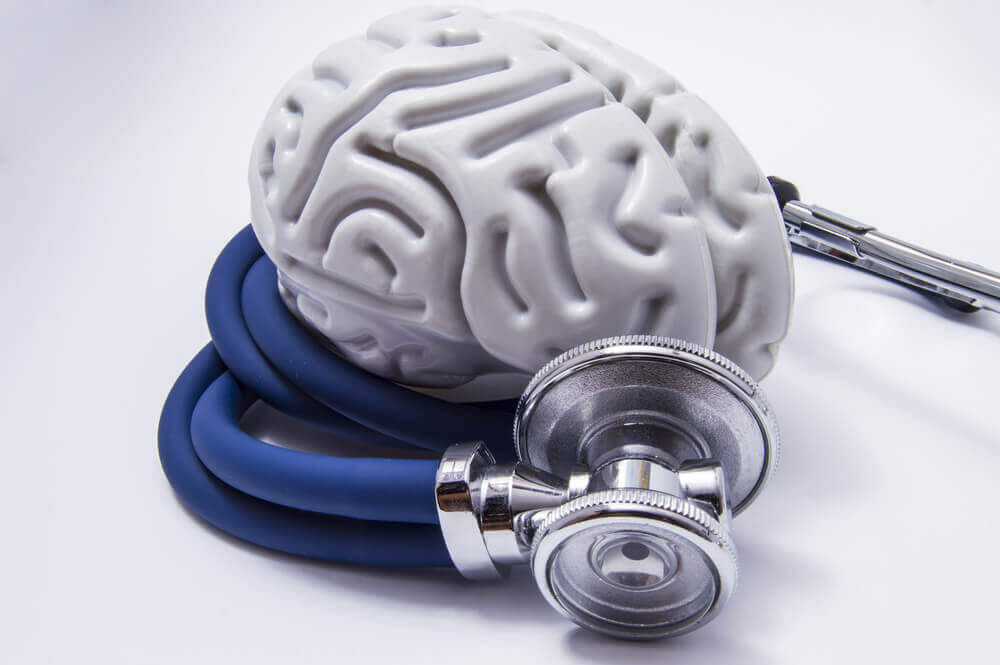 A stethestocope wrapped around a plastic model of the brain.