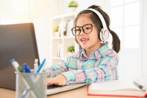 A girl seated in front of a computer.