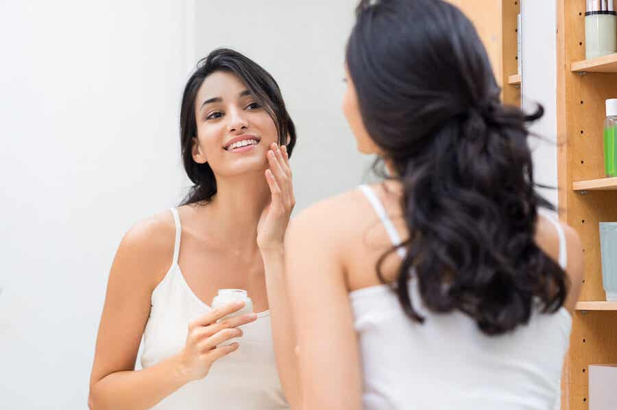 A woman putting on face cream