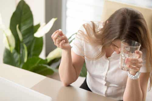 A woman taking a dose of an antimigraine drug