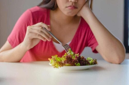 A woman trying to eat a salad.