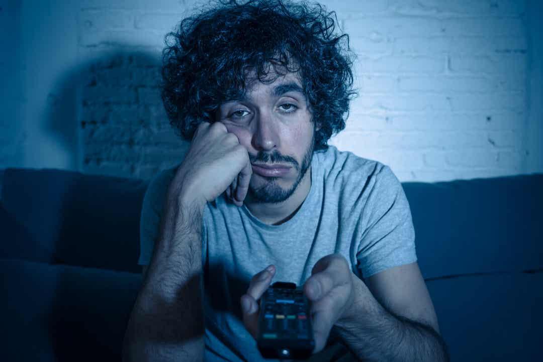 Karanlıkta televizyon izlerken sıkılan bir adam.