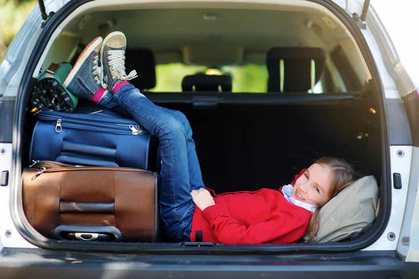A child resting in the back of a parked car with her legs on the suitcases.