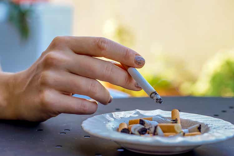 A person holding a cigarette over and ashtray full of cigarette butts.