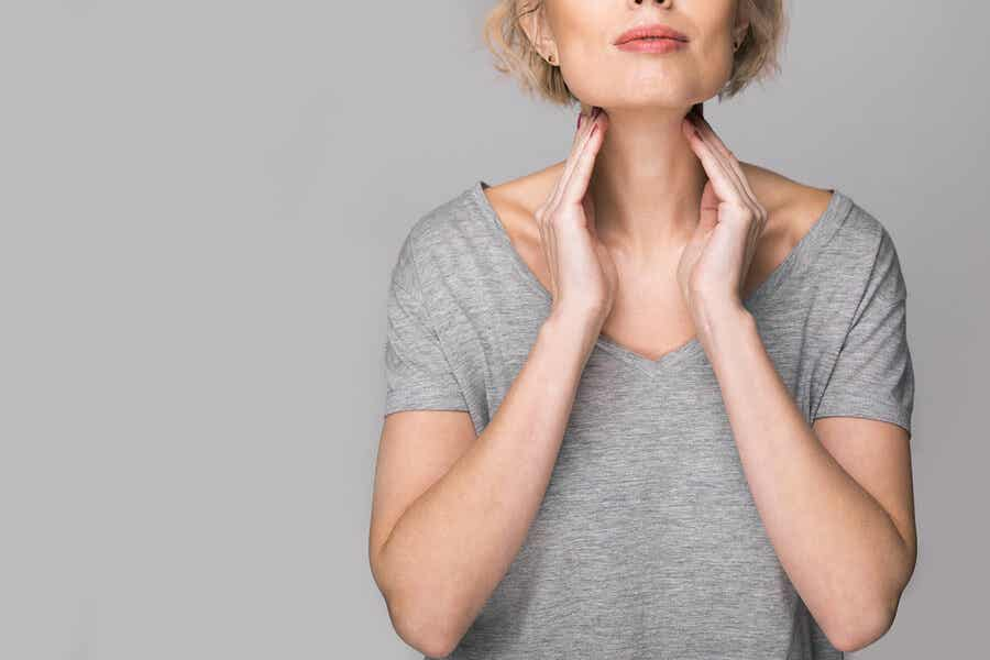 A woman palpating her neck to check her lymph nodes.