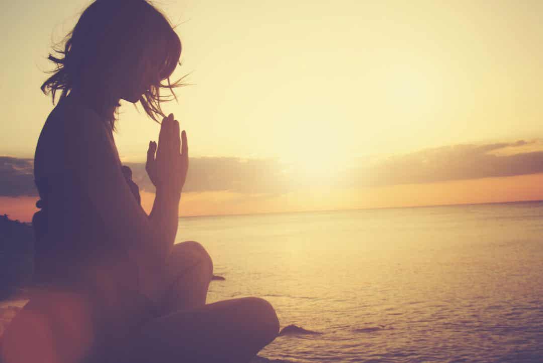 Gün batımında sahilde meditasyon yapan bir kadın.