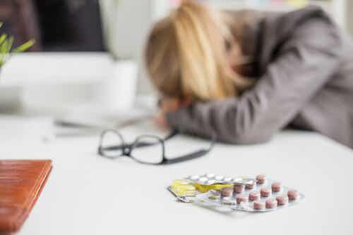 A woman resting her head on her desk, with various different medications in the foreground.